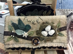 Clutch with built in coin purse pocket. Appliqued boiled wool detailing.